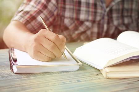 hand of people, student writing and note on notebook on wood table with copy space, in library, concept as education attempt and make effort to win, intend to improve knowledge for future life