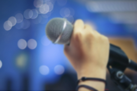 electronic music: Defocused and blur of hand holding microphone on bokeh background, concept as music instrument in studio room and meeting hall Stock Photo