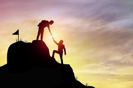 les gens de la silhouette aidant la main à gravir la roche de la montagne, le concept comme gagnant, l'amélioration et l'objectif du succès dans les affaires et le sport