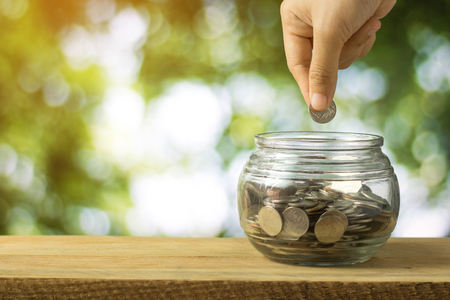 hand stacked money coins  on wood table and  green bokeh background, concept as finance, saving and capital banking 스톡 콘텐츠