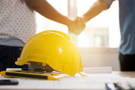 Conceito de trabalho em equipe, equipe de arquitetura agitando a mão na construção de constrangimentos, foco no capacete de segurança Foto de archivo - 89963909