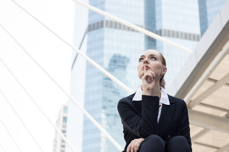Businesswomen sitting on stair outside building and thinking and planning to future Фото со стока