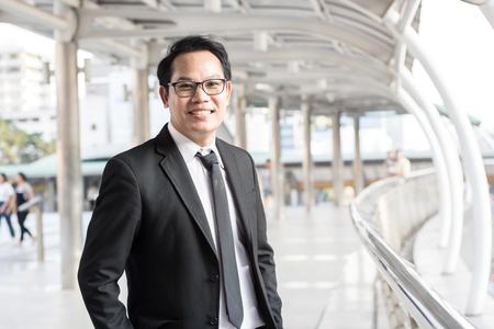 Happy businessman standing on walkway of building