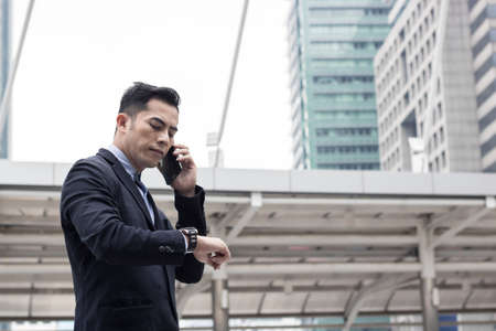 Businessman calling phone outside of building for connection and communication and watching watch