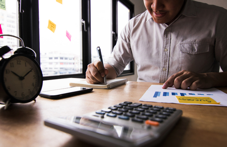 businesswomen writing and memory on notebook and calculator on table, accountant and business concept