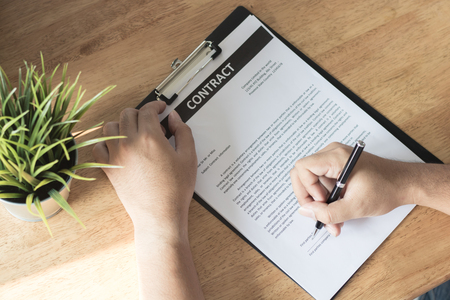Businessman signing on contract paper on table after accepted deal and agreement