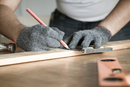 carpenter measuring and writing on wood with copy space background Фото со стока