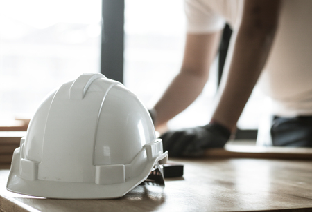 focus at safty helmet on working desk and carpenter on table