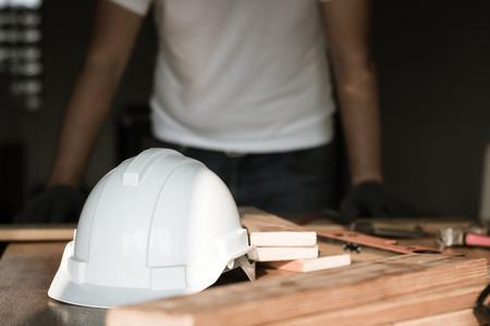 focus at safty helmet on working desk and carpenter background