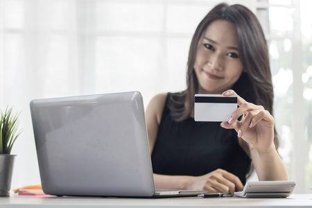 online shopping banner, women looking for buying goods in website on laptop and paying with credit casd on table at home