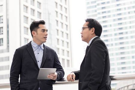 Businessman presenting work to boss, leader about planning project by laptop outside building