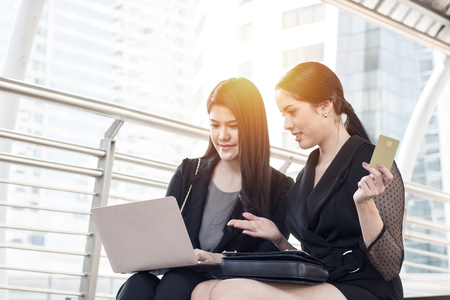 shopping online and lifestyle concept, two women looking on laptop and holding credit card for buying by searching internet