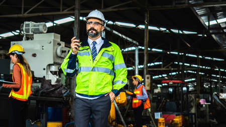 Portrait of successful middle aged Caucasian engineer manager wearing white helmet holding  radio communication to control worker and check business in industry