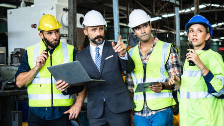 Industrial engineer in suite and safety helmet working in factory, planning and training with tablet with workers