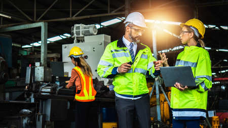 Male and female industrial engineers in hard hats discuss and plan new project while using laptop. inspection of engineer, inspector check and work in factory, checking and control with technology Archivio Fotografico