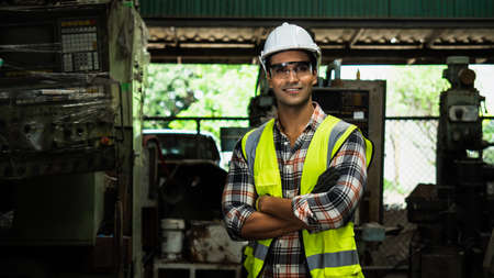 portrait handsome engineer in a factory, middle eastern smiling worker wearing white hat with green safety vest in industrial