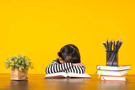 Kid sleep on table with lots of books on yellow background in studio