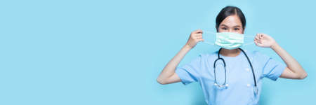 Portrait of young Asian beautiful nurse in blue uniform and wearing a surgical mask for protection from covid19 or coronavirus disease isolated in blue studio background. Archivio Fotografico