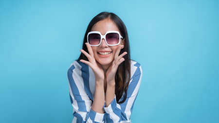 Beautiful woman wearing red glasses in blue modern fashion clothe holding megaphone and shouted in studio on blue background, be presented your product.