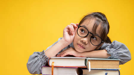 Thai Asian girl student fall down on stacked book, wearing glasses and looking camera in studio on orange or yellow background Archivio Fotografico