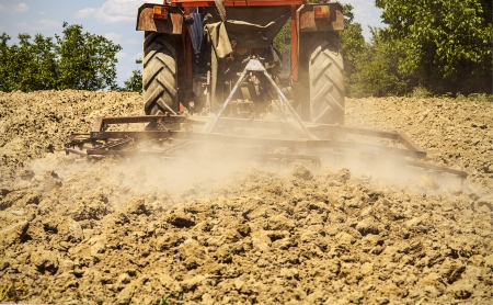 harrowing: tractor harrowing the land Stock Photo