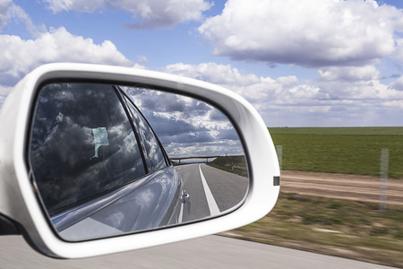 Rear view mirror reflecting freeway with cloud