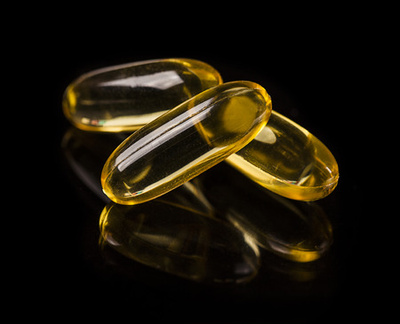 Cod liver oil omega 3 gel capsules on the dark glass Stock Photo - 43762394