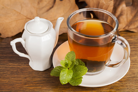 Teacup with fresh green tea with leaves in background