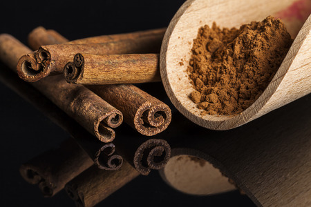 reflective: Cinnamon sticks and wooden spoon on dark reflective background Stock Photo
