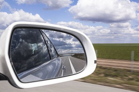 rear view mirror: Rear view mirror reflecting freeway with cloud