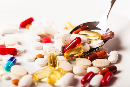 food poison: Colorful capsules with spoon Stock Photo