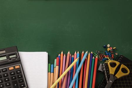 School supplies on green board background