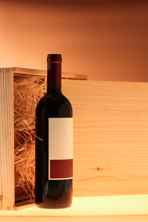 Wooden case with red wine bottle Stock Photo