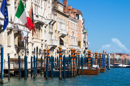 Venice Grand Canal mooring poles and taxi with European and Italian Flag