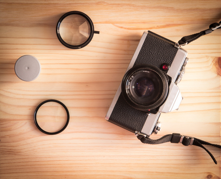 Retro vintage old photo camera with roll and lenses on a wooden table photo