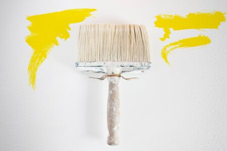 redecorate: Dirty wall brush Painting with yellow paint Stock Photo