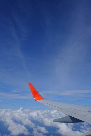 Aile d'avion avec un beau ciel bleu et des nuages depuis la fenêtre de l'avion, voyageant à l'étranger Banque d'images