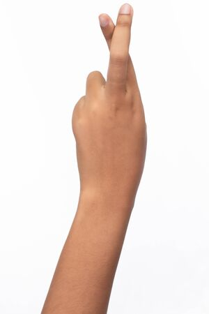 A hand of woman crossed finger, a gesture commonly used to wish for luck, isolated on white background
