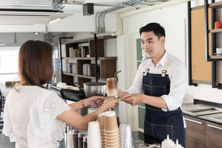 Smiling Asian barista man holding cup of ice beverage to show the customers in the coffee shop