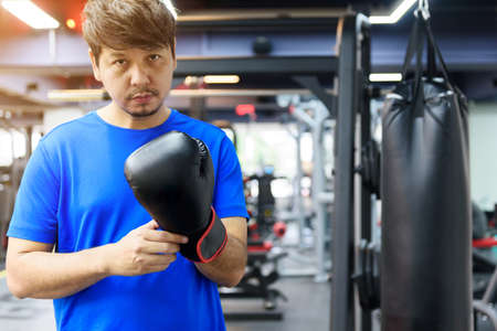 Handsome Asian man wears a blue sport shirt with black boxing gloves in the gym look at camera, there is sandbag on the background, sport and workout concept