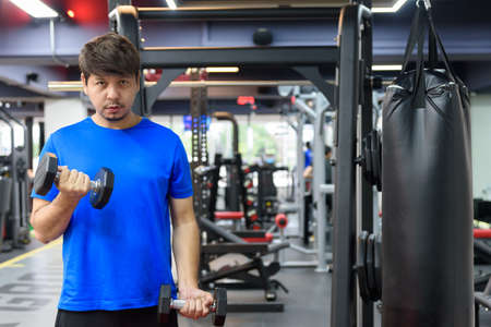 Handsome Asian man wears a blue sport shirt workout with dumbbells in the gym, there is sandbag on the background, sport and workout concept