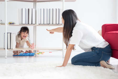 Young Asian mother taught her little daughter about reading English characters, having fun together, family concept