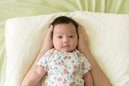 Top view of a cute Asian baby girl wrapped up in bed