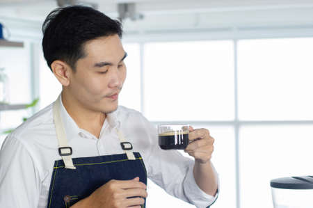 Asian barista man holding a cup of  black coffee, prepare to make coffee, serve customers in the coffee shop