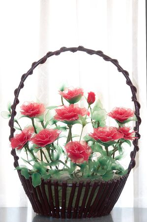 a picture of brown basket full of roses with white curtain behind