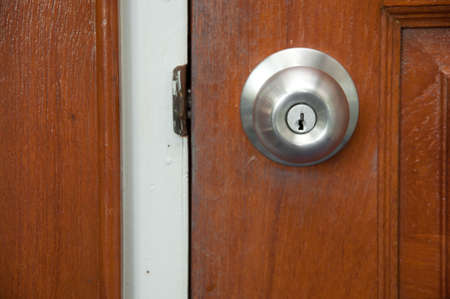 a picture of door knob with a wooden door photo