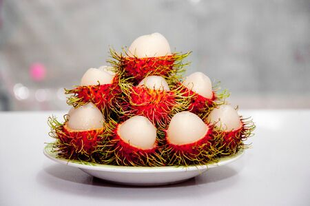 a picture of delicious red rambutan fruit peeled in plate photo