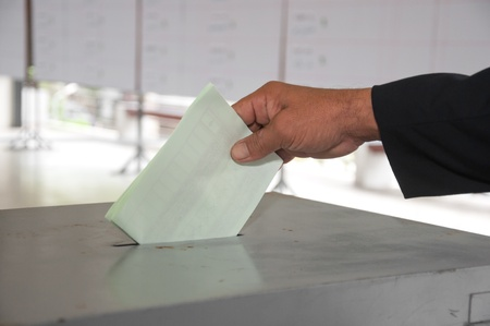 hand put voting paper Stock Photo