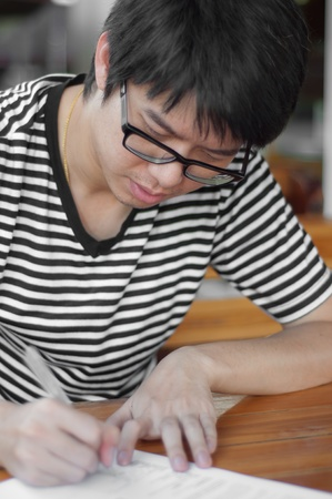 smiled: asian thai chinese smiled smart man with glasses writing Stock Photo