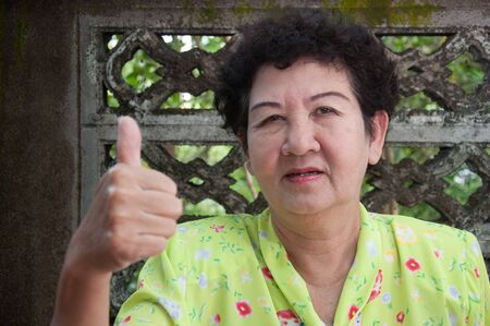 asian senior thai woman - thumb up hand sign concept photo